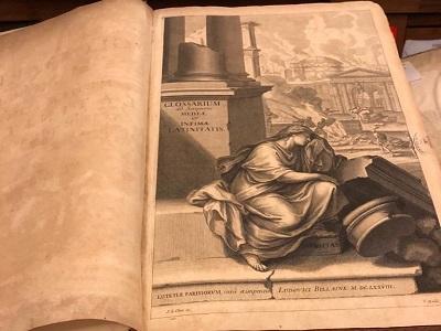 L'incisione che apre il Glossarium rappresenta una figura femminile (la Latinità) e sullo sfondo l'Urbe in fiamme.