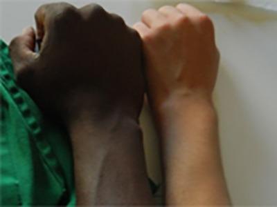 Le braccia di due ragazzi, uno nero e uno bianco, a confronto illustrano l'articolo che disciplina il divieto delle espulsioni collettive di stranieri all'interno della Convenzione CEDU